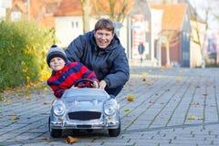 Kleinkindjunge und -vater, die mit Auto, draußen spielen Lizenzfreie Stockfotografie