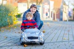 Kleinkindjunge und -vater, die mit Auto, draußen spielen Lizenzfreie Stockfotos