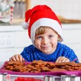 Kleinkindjungenbacken Weihnachtsplätzchen zu Hause Stockfotos