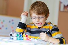 Kleinkindjungenzeichnung mit bunten Aquarellen zuhause Lizenzfreies Stockfoto
