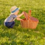 Kleinkindkind draußen Ein tragender Strohhut des jährigen Babys, der im Picknickkorb schaut stockfotos