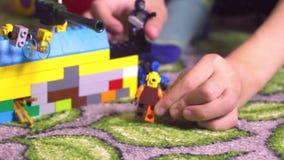 Kleinkindkinderkleiner Junge mit blondi Haarsitzen umgeben durch Spielwaren und das Spielen mit Bausteine lego menschlicher Figur stock video