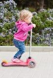 Kleinkindmädchen auf einem Roller in einem Park Lizenzfreies Stockbild