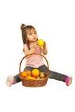 Kleinkindmädchen, das Apfel vom Korb gibt Stockfotos