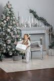 Kleinkindmädchen, das auf dem Raum mit Weihnachtsbaum und Geschenken bleibt stockfotos