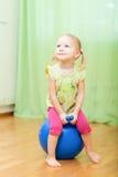 Kleinkindmädchen, das auf Kugel springt Lizenzfreie Stockfotos