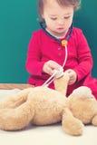 Kleinkindmädchen, das für ihren Teddybären mit einem Stethoskop sich interessiert Stockfoto