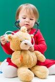 Kleinkindmädchen, das für ihren Teddybären mit einem Stethoskop sich interessiert Stockbild