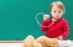 Kleinkindmädchen, das für ihren Teddybären mit einem Stethoskop sich interessiert Stockfotos
