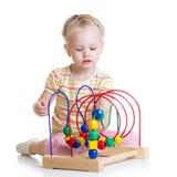 Kleinkindmädchen, das mit buntem Spielzeug spielt Stockfotos