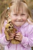 Kleinkindmädchen, das mit einem Häschenspielzeug lächelt stockfotos