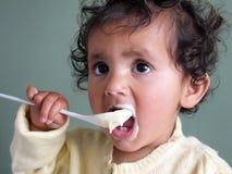 Kleinkindmädchen, das mit einem Löffel des Breis sich einzieht Stockbilder