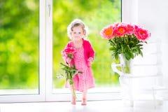 Kleinkindmädchen, das mit Pfingstrosenblumen spielt Stockbilder