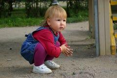 Kleinkindmädchen, das mit Sand spielt Stockbild