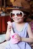 Kleinkindmädchen, das Spaß mit Spielzeuggitarre in den Armen und in der Sonnenbrille auf Gesicht hat lizenzfreie stockfotografie