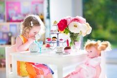 Kleinkindmädchen, das Teeparty mit einer Puppe spielt Stockbilder