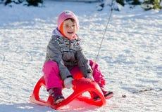 Kleinkindmädchen in der Winterklage auf dem Pferdeschlitten, der Spaß hat Stockfoto