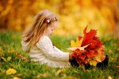 Kleinkindmädchen haben Spaß mit gefallenen goldenen Blättern Lizenzfreies Stockfoto