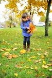Kleinkindmädchen im blauen Mantel, der aufhebt, verlässt lizenzfreies stockfoto
