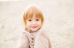Kleinkindmädchen mit dem roten Haar eingewickelt in einem Tuch am Strand Stockfoto
