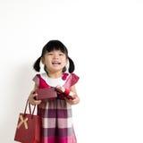 Kleinkindmädchen mit Geschenkbox und Tasche Lizenzfreies Stockfoto