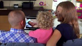 Kleinkindmädchen mit Mutter und Vati passen Familienfilm auf Tablet-Computer auf stock video footage
