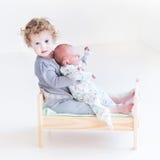 Kleinkindmädchen mit neugeborenem Babybruder im Spielzeugbett stockbild