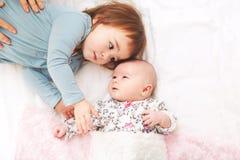 Kleinkindmädchen, das mit ihrer neugeborenen Schwester spielt Lizenzfreie Stockbilder