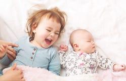 Kleinkindmädchen, das mit ihrer neugeborenen Schwester spielt Lizenzfreie Stockfotografie
