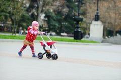 Kleinkindmädchen mit Spielzeugspaziergänger Lizenzfreies Stockfoto
