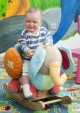 Kleinkindschätzchen auf einem Schwingspielzeug Lizenzfreie Stockbilder