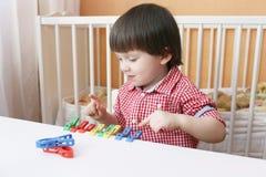 Kleinkindspiele mit Kleidungsstiften zu Hause Lizenzfreie Stockfotos