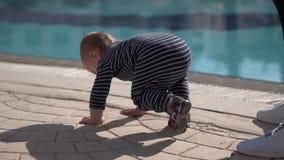 Kleinkindstand und -fall in Zeitlupe nahe Pool stock footage