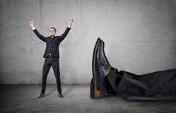 Kleinunternehmer, der mit seinen Armen herauf nahes riesiges Bein eines anderen Mannes steht stockbild