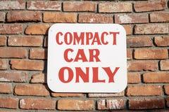 Kleinwagen, der nur Zeichen auf Backsteinmauer parkt stockbild