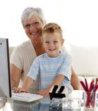 Kleinzoon die een computer met zijn grootmoeder met behulp van Royalty-vrije Stock Fotografie