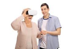 Kleinzoon die grootmoeder tonen hoe te om een VR-hoofdtelefoon te gebruiken Royalty-vrije Stock Foto