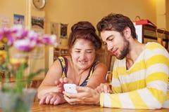 Kleinzoon die zijn grootmoeder onderwijzen hoe te om mobiele telefoon te gebruiken Stock Foto's