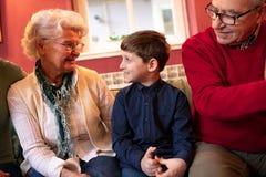 Kleinzoon die zijn grootouders voor vakantie bezoeken stock afbeelding