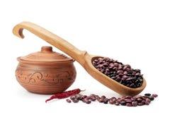 Kleipot, houten lepel, bonen en kruiden Stock Foto