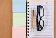 kleista notatka, ballpoint pióro, pusty notatnik, eyeglasses na biurze Fotografia Stock