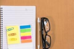 kleista notatka, ballpoint pióro, pusty notatnik, eyeglasses na biurze Obraz Royalty Free