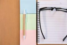 kleista notatka, ballpoint pióro, pusty notatnik, eyeglasses na biurze Obraz Stock