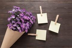 Kleiste notatki są na drewnianym tle z purpurowym krajacza flo Zdjęcia Stock