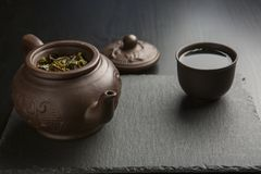 Kleitheepot met het hoogtepunt van de kleikop van groene thee op zwarte leiachtergrond royalty-vrije stock foto