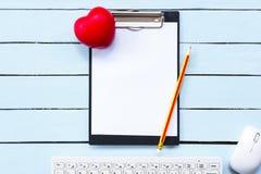 Klembord en rood hart met potlood en toetsenbord op blauwe houten lijst Het concept van de gezondheid Stock Afbeeldingen