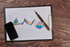 Klembord met 3d grafieken, smartphone en pen Stock Fotografie