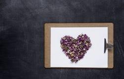 Klembord met en een hart van bloemen op zwarte achtergrond Valen Royalty-vrije Stock Foto's