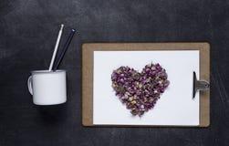 Klembord met en een hart van bloemen op zwarte achtergrond Valen Royalty-vrije Stock Afbeeldingen