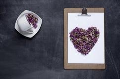Klembord met en een hart van bloemen op zwarte achtergrond Valen Stock Afbeelding